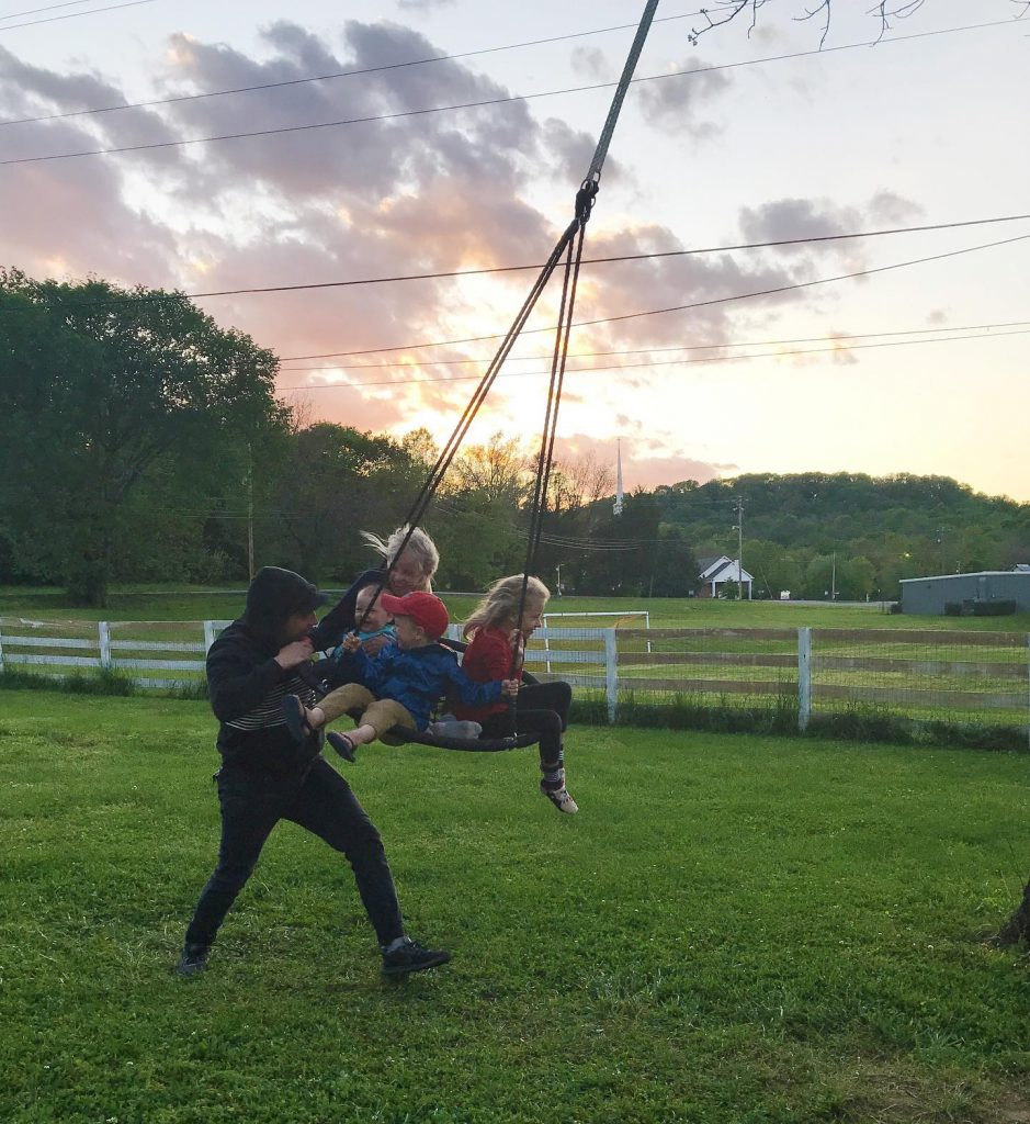 Dad pushing his 4 children on a large swing with a beautiful sunset in background