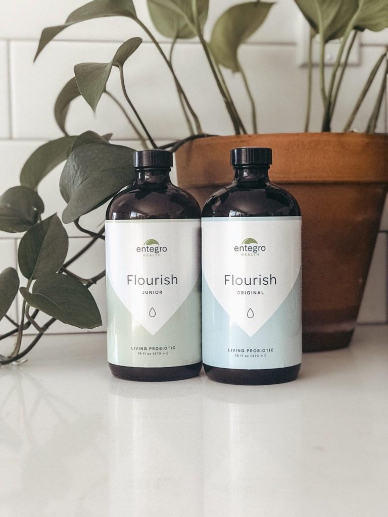 two bottles of Flourish probiotics in front of plant