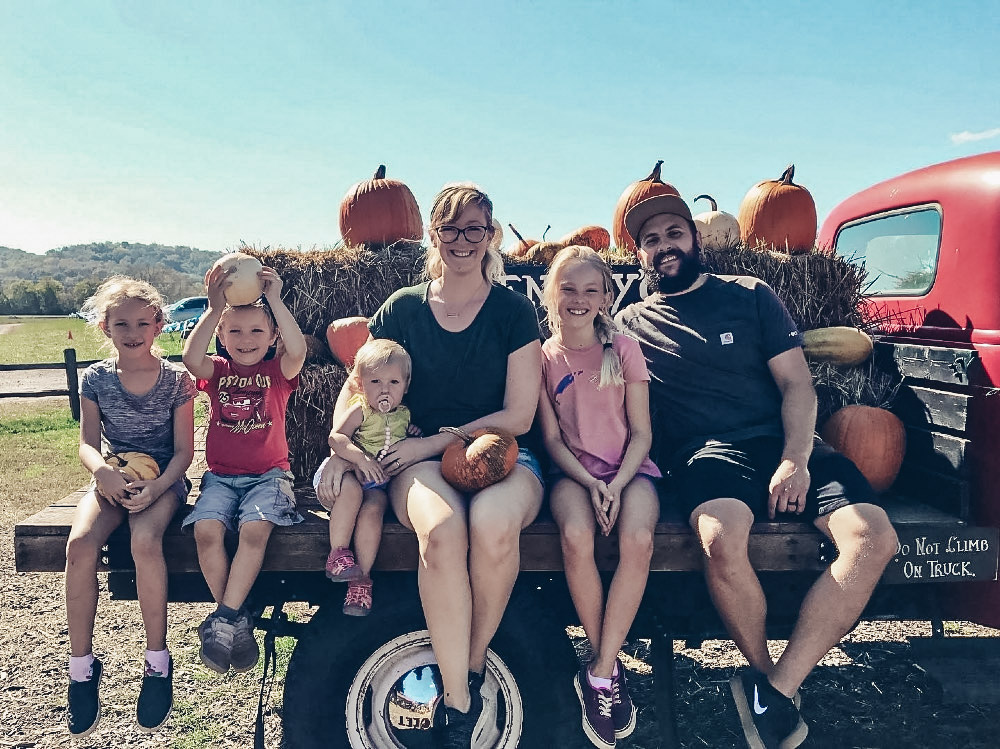 family of 6 sitting on back of pick up truck with pumpkins
