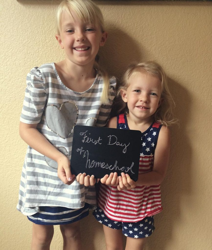two young girls holding first day of homeschool sign