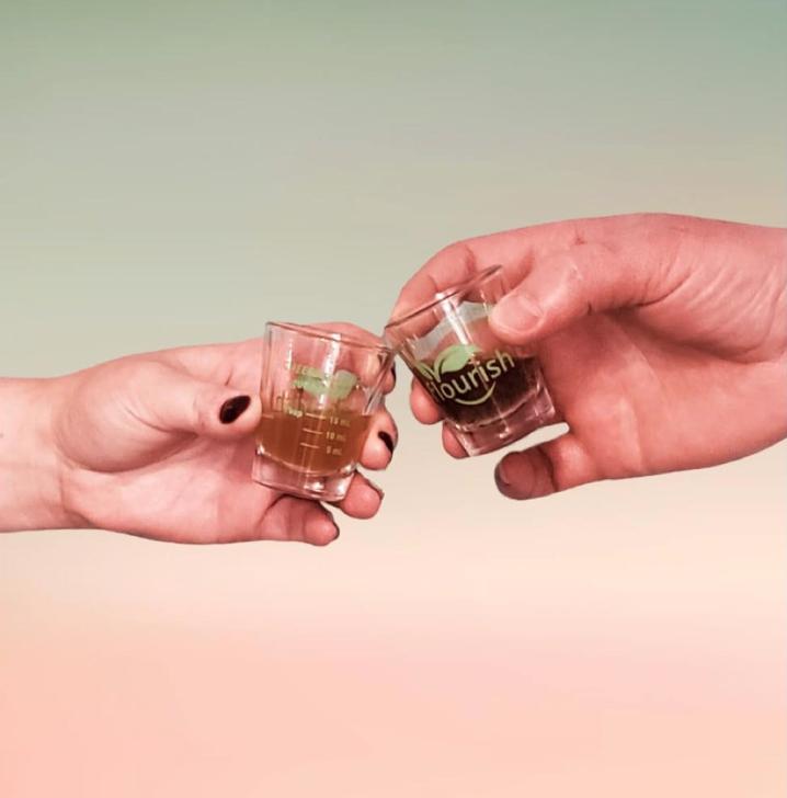 two hands holding liquid living probiotics in shot glasses