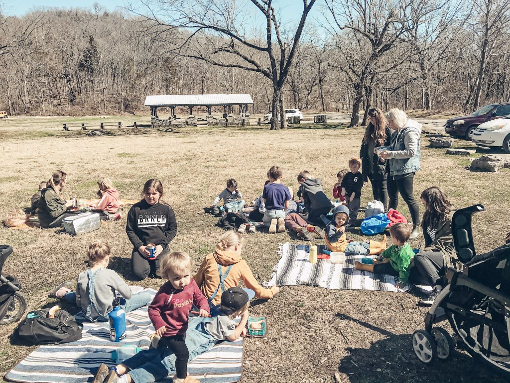 homeschooling families gathered for nature co op sitting on blankets in the grass