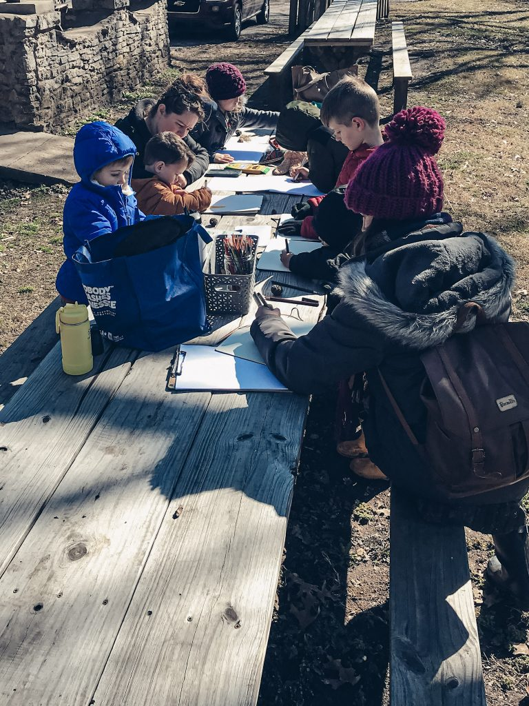 Nature study taking place at picnic tables with people wearing winter clothing