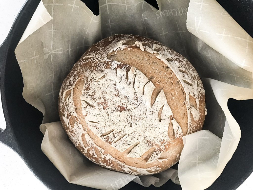 loaf of GF sourdough bread in cast iron dutch oven