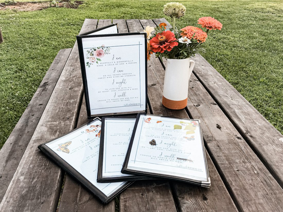 homeschool morning time menus laid on a picnic table with a vase of flowers