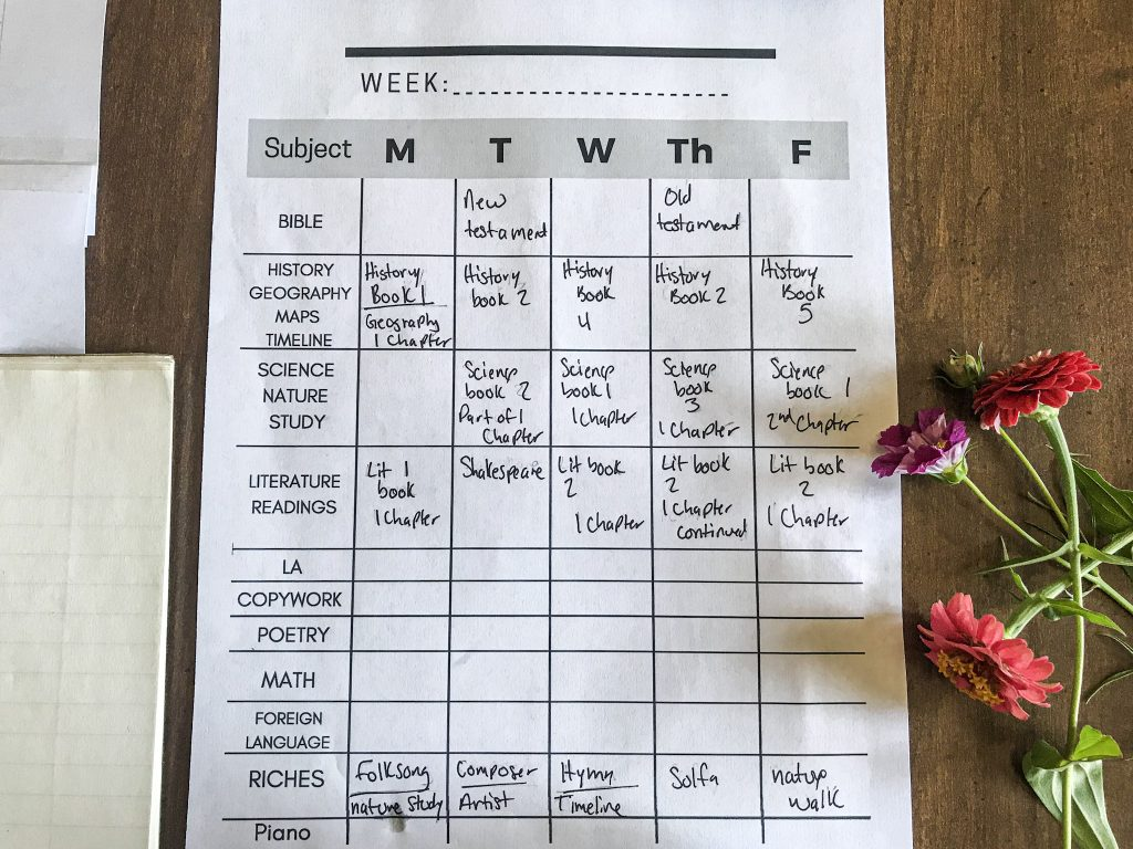 close up image of filled out Charlotte Mason weekly schedule with flowers on table